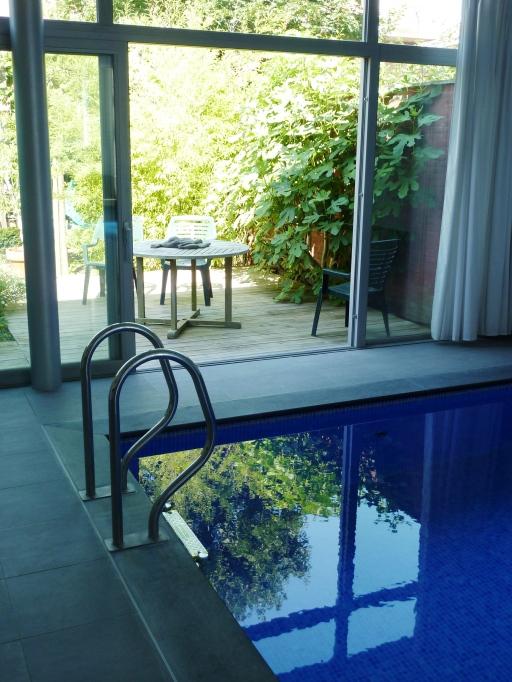 zicht van zwembad naar terrras - Inblauw bed & breakfast